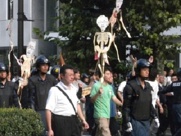 2011年8月15日、先帝陛下(昭和天皇)の似顔絵に骸骨を付けた人形を振り回しながらのデモ行進する「パジャマ男」=柏崎正憲